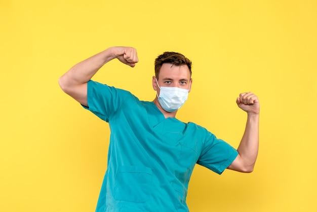 Vorderansicht des männlichen arztes, der in der sterilen maske auf gelber wand biegt