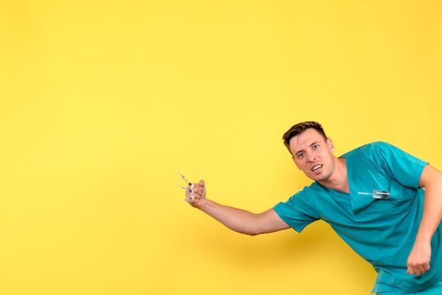 Vorderansicht des männlichen arztes, der injektionen an gelber wand hält