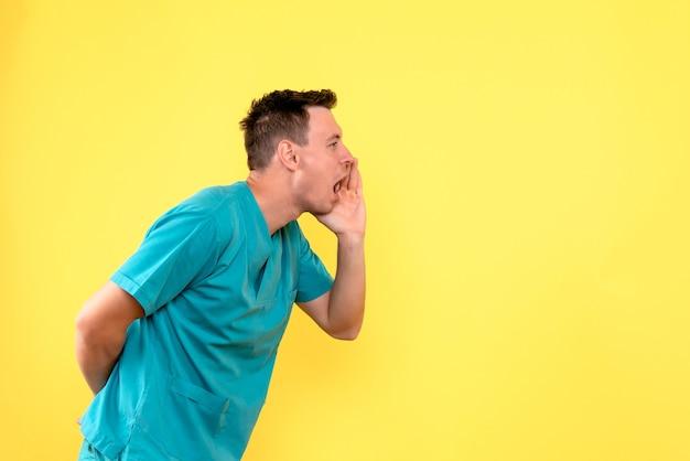Vorderansicht des männlichen arztes, der jemanden auf gelber wand anruft