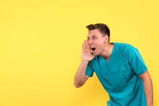 Vorderansicht des männlichen arztes, der laut auf gelbe wand ruft