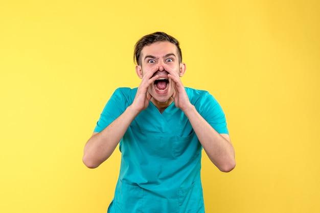 Vorderansicht des männlichen arztes, der laut gelbe wand anruft