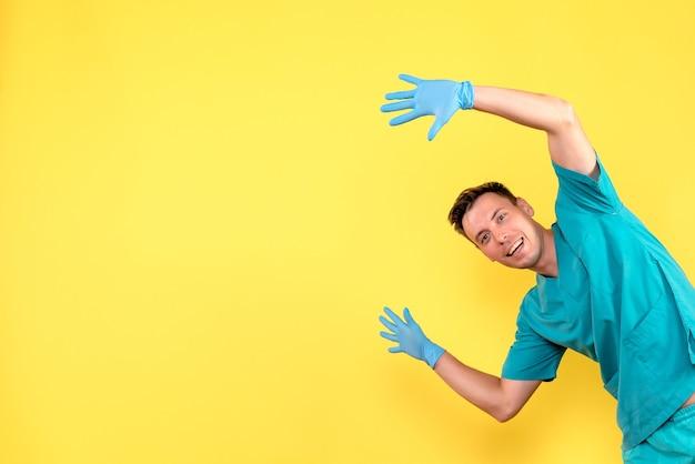 Vorderansicht des männlichen arztes, der mit blauen handschuhen auf gelber wand aufwirft