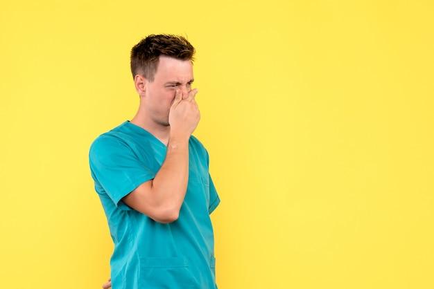Vorderansicht des männlichen arztes, der seine nase auf gelber wand bedeckt