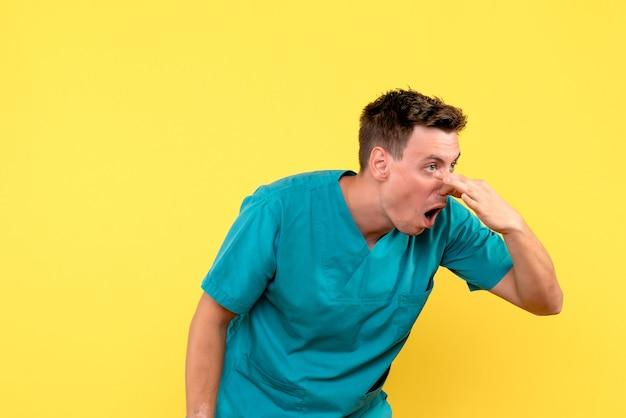 Vorderansicht des männlichen arztes, der seine nase auf gelber wand schließt