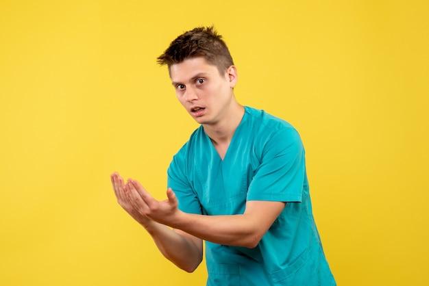 Vorderansicht des männlichen arztes im medizinischen anzug auf gelber wand