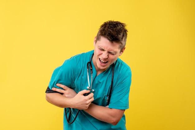 Vorderansicht des männlichen arztes im medizinischen anzug, der seinen druck auf gelbe wand prüft