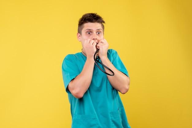 Vorderansicht des männlichen arztes im medizinischen anzug mit dem stethoskop, das auf gelber wand erschreckt wird