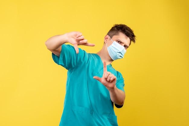 Vorderansicht des männlichen arztes im medizinischen anzug mit steriler maske auf gelber wand
