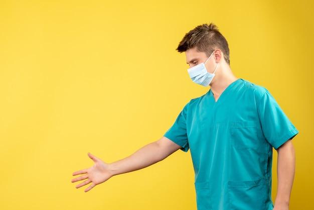 Vorderansicht des männlichen arztes im medizinischen anzug mit steriler maske, die hände auf gelber wand schüttelt