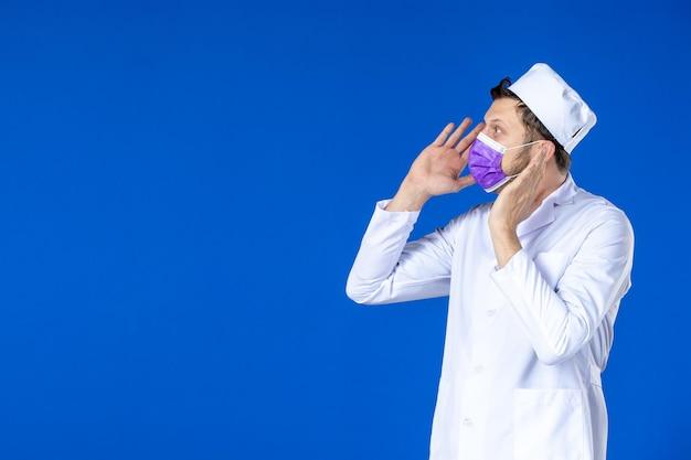 Vorderansicht des männlichen arztes im medizinischen anzug und in der lila maske auf blau