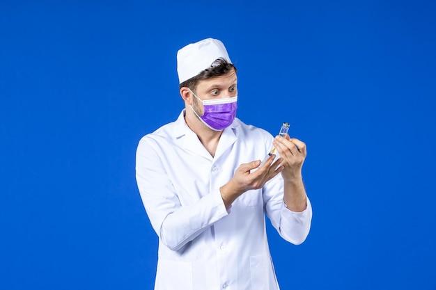 Vorderansicht des männlichen arztes im medizinischen anzug und in der maske, die impfstoff und injektion auf blau halten