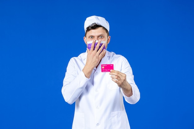 Vorderansicht des männlichen arztes im medizinischen anzug und in der maske, die kreditkarte auf blau hält