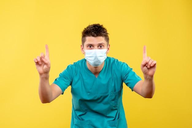 Vorderansicht des männlichen arztes im medizinischen anzug und in der schutzmaske auf gelber wand
