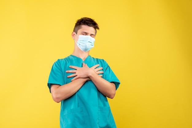 Vorderansicht des männlichen arztes im medizinischen anzug und in der sterilen maske auf gelber wand