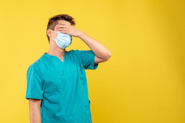 Vorderansicht des männlichen arztes im medizinischen anzug und in der sterilen maske enttäuscht auf gelber wand