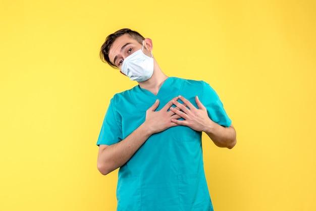 Vorderansicht des männlichen arztes in der maske auf gelber wand