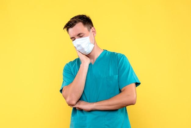 Vorderansicht des männlichen arztes in der sterilen maske auf gelber wand