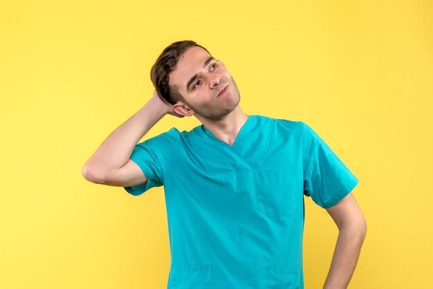 Vorderansicht des männlichen arztes mit gestresstem gesicht auf gelber wand
