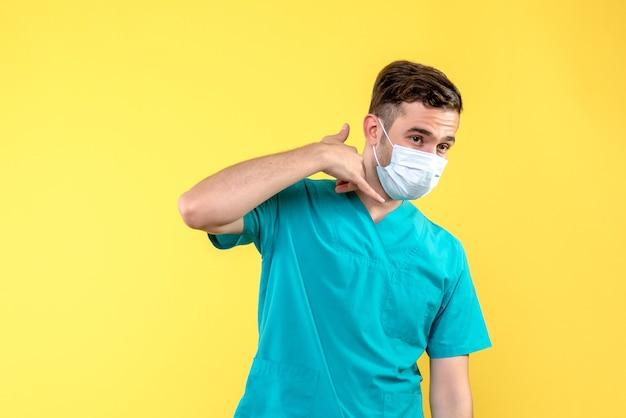 Vorderansicht des männlichen arztes mit steriler maske auf gelber wand