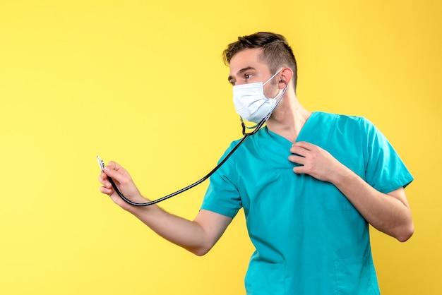 Vorderansicht des männlichen arztes mit stethoskop und maske auf gelber wand