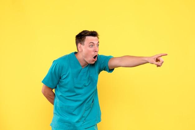 Vorderansicht des männlichen arztes mit überraschtem ausdruck auf gelber wand