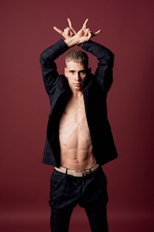 Vorderansicht des männlichen ausführenden aufwerfend in der klage ohne hemd und offenen blazer