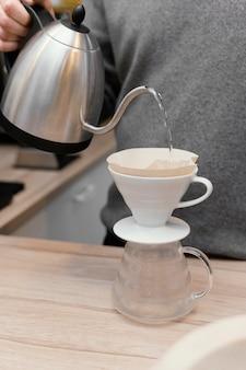 Vorderansicht des männlichen barista, der am kaffeehaus arbeitet