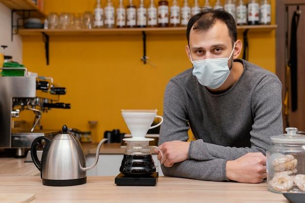Vorderansicht des männlichen barista mit der medizinischen maske, die im kaffeehaus aufwirft