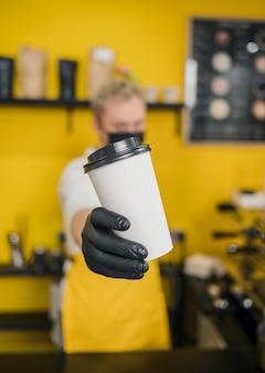 Vorderansicht des männlichen barista mit der medizinischen maske, die kaffeetasse hält
