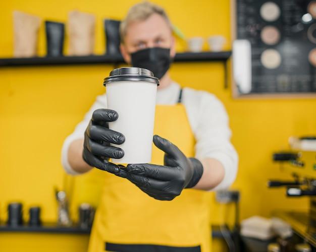 Vorderansicht des männlichen barista mit medizinischer maske und handschuhen, die kaffeetasse halten