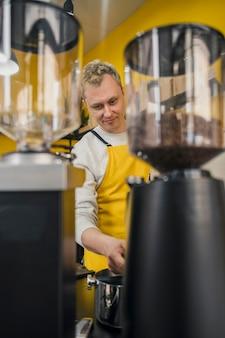 Vorderansicht des männlichen barista mit schürze bei der arbeit