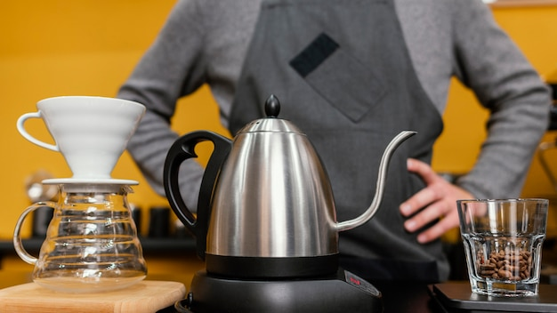Vorderansicht des männlichen barista mit schürze, die kaffee mit kessel und filter vorbereitet