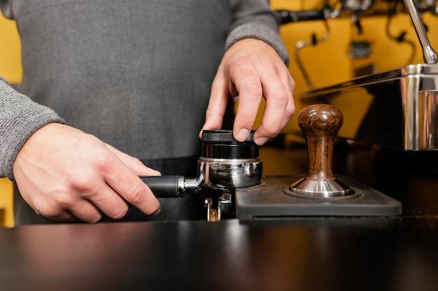 Vorderansicht des männlichen barista unter verwendung der professionellen kaffeemaschinenschale