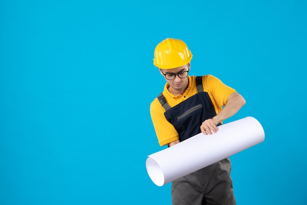 Vorderansicht des männlichen baumeisters in der gelben uniform auf blau