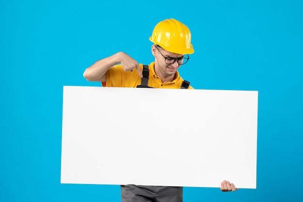 Vorderansicht des männlichen baumeisters in der gelben uniform mit plan auf blau