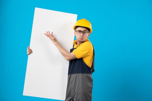 Vorderansicht des männlichen baumeisters in der gelben uniform und im helm auf der blauen wand