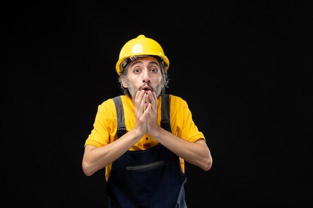 Vorderansicht des männlichen baumeisters in gelber uniform an der schwarzen wand