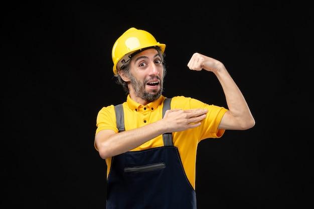 Vorderansicht des männlichen baumeisters in gelber uniform, der sich an schwarzer wand biegt