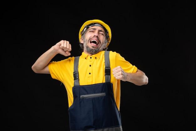 Vorderansicht des männlichen baumeisters in uniform, der auf schwarzer wand gähnt