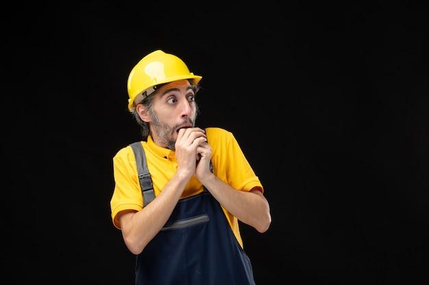 Vorderansicht des männlichen baumeisters in uniform erschrocken an schwarzer wand