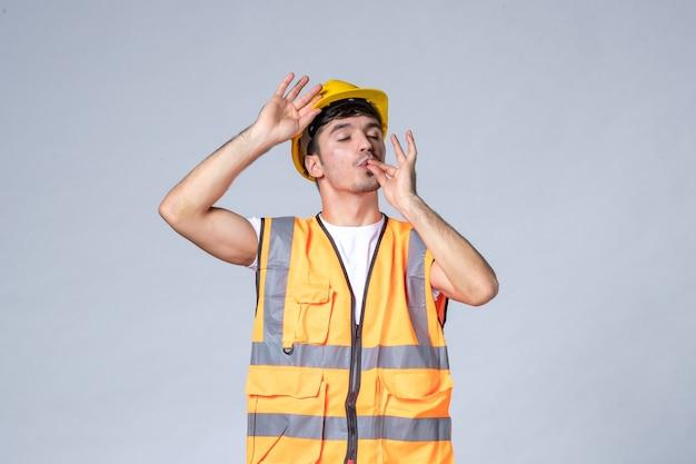 Vorderansicht des männlichen baumeisters in uniform mit schutzhelm auf weißer wand
