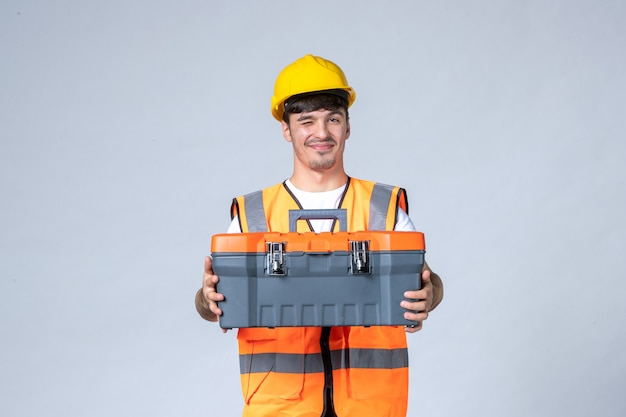 Vorderansicht des männlichen baumeisters in uniform und gelbem helm mit werkzeugkoffer an weißer wand