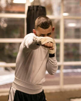 Vorderansicht des männlichen boxers, der mit boxsack übt