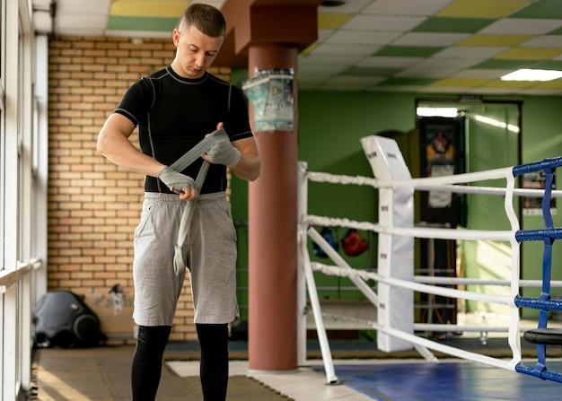 Vorderansicht des männlichen boxers, der seine hände vor dem training im boxring einwickelt