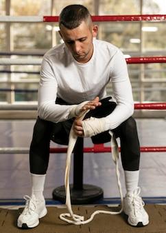 Vorderansicht des männlichen boxers, der seine hände vor dem training im ring einwickelt