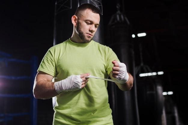 Vorderansicht des männlichen boxers im t-shirt, das auf schutz für hände sich setzt