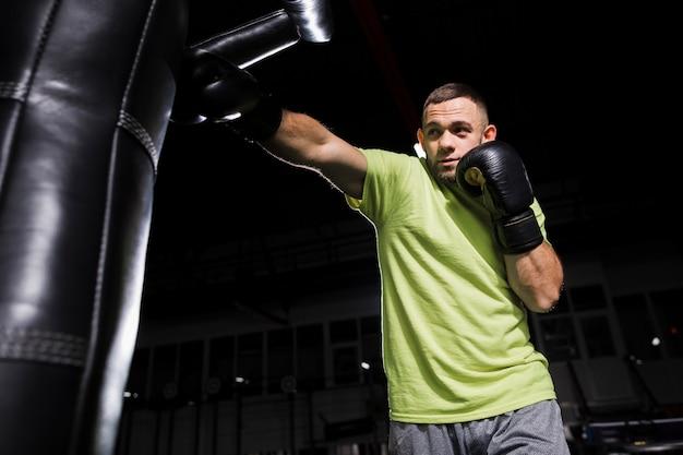 Vorderansicht des männlichen boxers übend mit sandsack