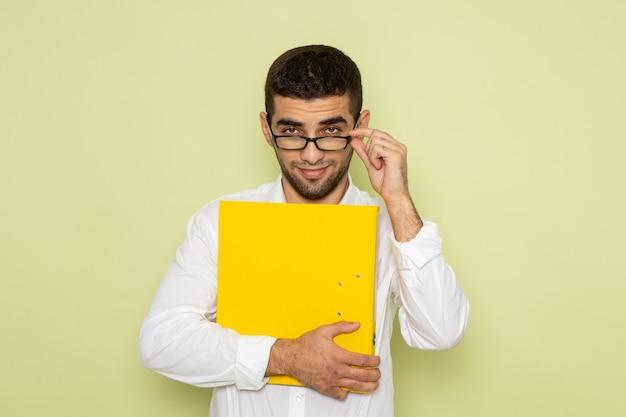 Vorderansicht des männlichen büroangestellten im weißen hemd, das gelbe datei auf der hellgrünen wand hält