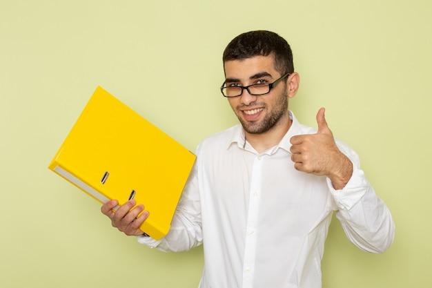 Vorderansicht des männlichen büroangestellten im weißen hemd, das gelbe dateien mit lächeln auf der grünen wand hält