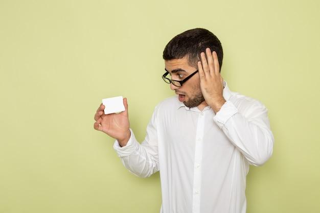 Vorderansicht des männlichen büroangestellten im weißen hemd, das karte auf der hellgrünen wand hält